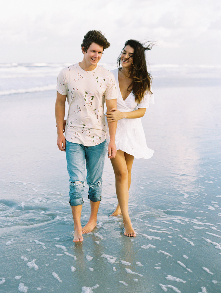 Romantic couple walking barefoot on the beach
