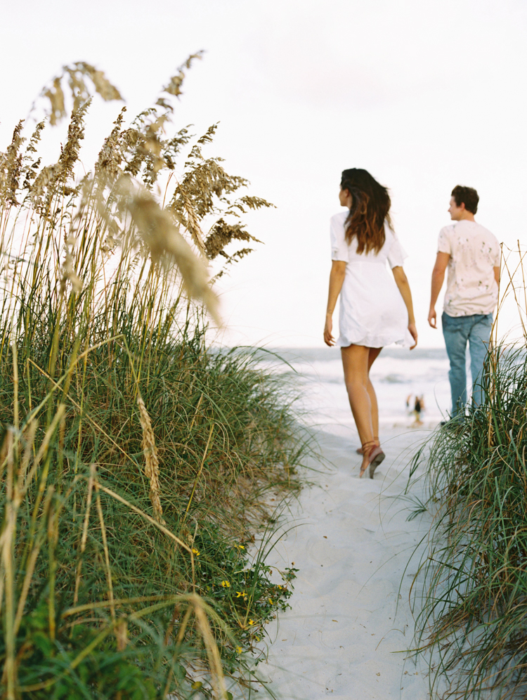 engaged couple walking through the dunes in atlantic beach
