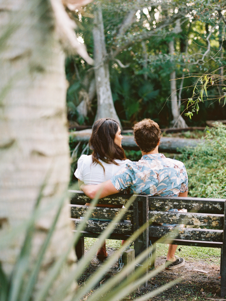 Engaged couple sitting on a bench in a florida garden