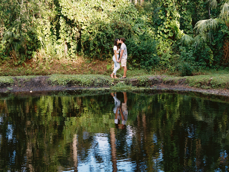 Romantic engagement photos next to pond in tropical Jacksonville gardens