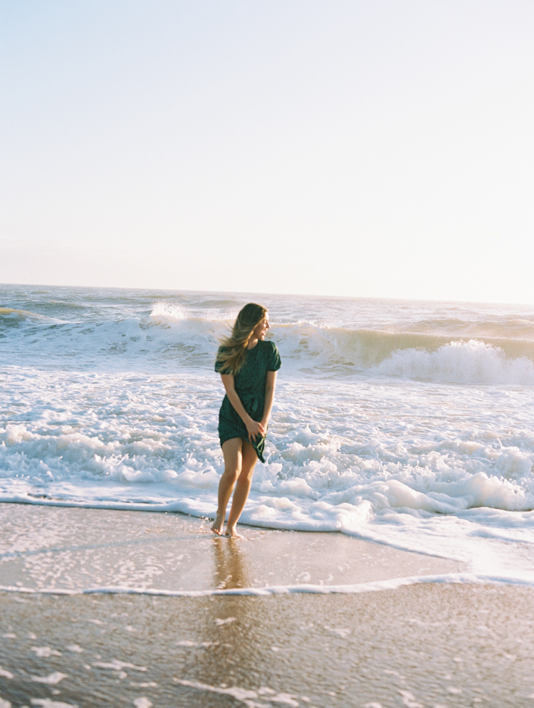 boho girl laughing and running away from ocean waves